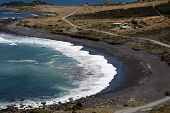 Remote Stony Beach With Road Traveling Around The Coastline poster