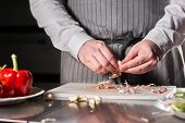Closeup Of Hand With Knife Cutting Fresh Vegetable. Young Chef Cutting Garlic On A White Cutting Boa poster