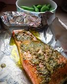 Beautiful slice of raw norwegian salmon with olive oil and green pesto in aluminium foil ready for b poster