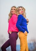 Sisters Enjoy Colorful Outfits On Gloomy Day Sky Background. Bright Mood. Bright Sweaters And Pants  poster