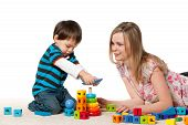 pic of babysitter  - Young mother and a little son are playing on the carpet with blocks - JPG