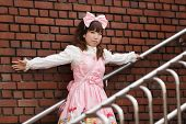 japanese lolita cosplay leaning against brick wall on stairs
