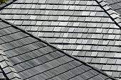 stock photo of shingles  - Several angled rooftops with worn and weathered wooden shingles - JPG