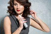 image of hairspray  - Beautiful girl laying fixes using hairspray  - JPG