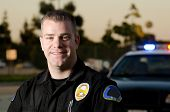 stock photo of policeman  - A smiling police officer in front of his patrol car - JPG