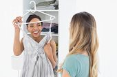 picture of slumber party  - Cheerful young woman showing a dress to her friend at home - JPG