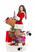 foto of flirtatious  - Sensual flirtatious young woman wearing sexy Santa costume holding a present bag in front of decorated Christmas tree and gifts isolated on white - JPG