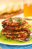 image of red shallot  - Vegetable and egg fritter made of zucchini red bell pepper eggs green onions and thyme piled on a green plate with fork on the side  - JPG