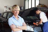 stock photo of car repair shop  - portrait of female client with arms folded in auto repair shop - JPG