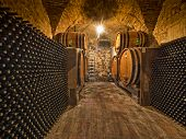 stock photo of liquor bottle  - wine bottles and barrels in a winery cellar - JPG