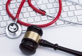 pic of judiciary  - Close up of wooden gavel and a stethoscope at the computer keyboard - JPG