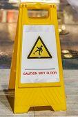 picture of slip hazard  - caution wet floor sign at a sidewalk - JPG