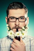 image of peace-pipe  - Handsome young man in glasses and a beard of flowers smoking a pipe - JPG