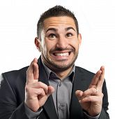 stock photo of fingers crossed  - Young businessman with his fingers crossing over white background - JPG