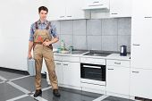 stock photo of pipe wrench  - Happy Young Plumber Holding Pipe Wrench In Kitchen Room - JPG