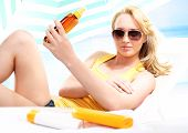picture of lubricant  - Young attractive blonde lubricates the skin balm with filter - JPG
