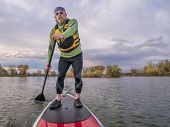 stock photo of collins  - senior paddler in life jacket enjoying stand up paddling on lake - JPG