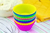 stock photo of cake-mixer  - Colorful silicone molds for cupcakes, mixer, yellow cloth potholder, the dough in a glass bowl on linen background