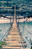 stock photo of shaky  - Scary shaky long footgbridge in Arunachal Pradesh region in India - JPG