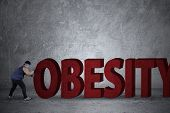 picture of obese man  - Full length of fat man in sportswear pushing an obesity word - JPG