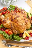 foto of roast chicken  - Whole roasted chicken garnished with fresh cucumbers wine tomatoes green salad and sage on dinner table - JPG