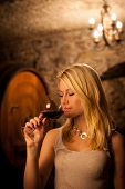 stock photo of wine cellar  - Beautiful young woman tasting red wine in a wine cellar - JPG