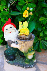 stock photo of  midget elves  - Gnome and frog with yellow flowers  - JPG