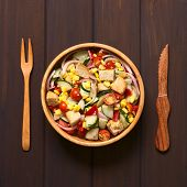 image of sweet-corn  - Overhead shot of fresh vegetable salad made of sweet corn cherry tomato cucumber red onion red pepper chives with croutons in wooden bowl photographed on dark wood with natural light - JPG