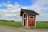 stock photo of bus-shelter  - Red wooden bus stop shelter and two mail boxes by rural road at summer - JPG