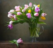 stock photo of jug  - Still life with colorful tulips in glass jug - JPG