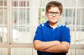 picture of arms race  - Cute young kid wearing glasses and casual clothes relaxing with his arms crossed at home - JPG