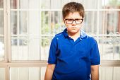 stock photo of pissed off  - Little blond kid with glasses looking all angry and pissed off at home - JPG