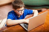 picture of tween  - High angle view of a little boy using a laptop computer for his homework - JPG