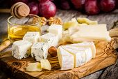 pic of brie cheese  - Cheese plate:Emmental Camembert Parmesan blue cheese bread sticks walnuts hazelnuts honey grapes