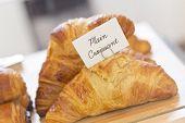 stock photo of croissant  - Tasty flaky plain croissants in bakery display case - JPG