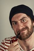 picture of wacky  - Mean bearded sailor grimacing while smoking a pipe - JPG