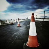 stock photo of road construction  - a traffic cone in a road under construction - JPG