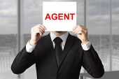 picture of incognito  - secret agent in black suit hiding face behind sign undercover - JPG