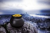 picture of pot gold  - pot of gold against large rock overlooking huge city - JPG