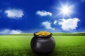 stock photo of pot gold  - pot of gold against sunny green landscape - JPG