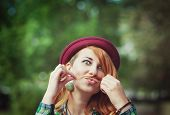 stock photo of moustache  - Hipster redhead woman making a moustache with her hair outdoor - JPG