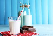 image of bittersweet  - Glass and bottles of milk with chocolate chunks on dots napkin and color wooden planks background - JPG