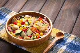 stock photo of sweet-corn  - Fresh vegetable salad made of sweet corn cherry tomato cucumber red onion red pepper chives with croutons in wooden bowl photographed on dark wood with natural light  - JPG