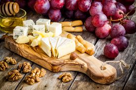 stock photo of hazelnut  - Cheese plate: Camembert Parmesan blue cheese bread sticks walnuts hazelnuts honey grapes on wooden table