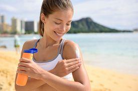 pic of sun tan lotion  - Sunscreen fitness woman applying suntan lotion - JPG