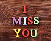 picture of missing  - Inscription I MISS YOU made of colorful letters on wooden background - JPG