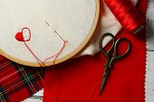 stock photo of sewing  - The embroidery hoop with canvas and red sewing threads on table close up - JPG