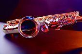 image of saxophones  - Golden saxophone on purple background - JPG