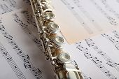 stock photo of flute  - Flute on music notes background - JPG