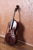 image of cello  - Classical cello and bow on brown wall background - JPG